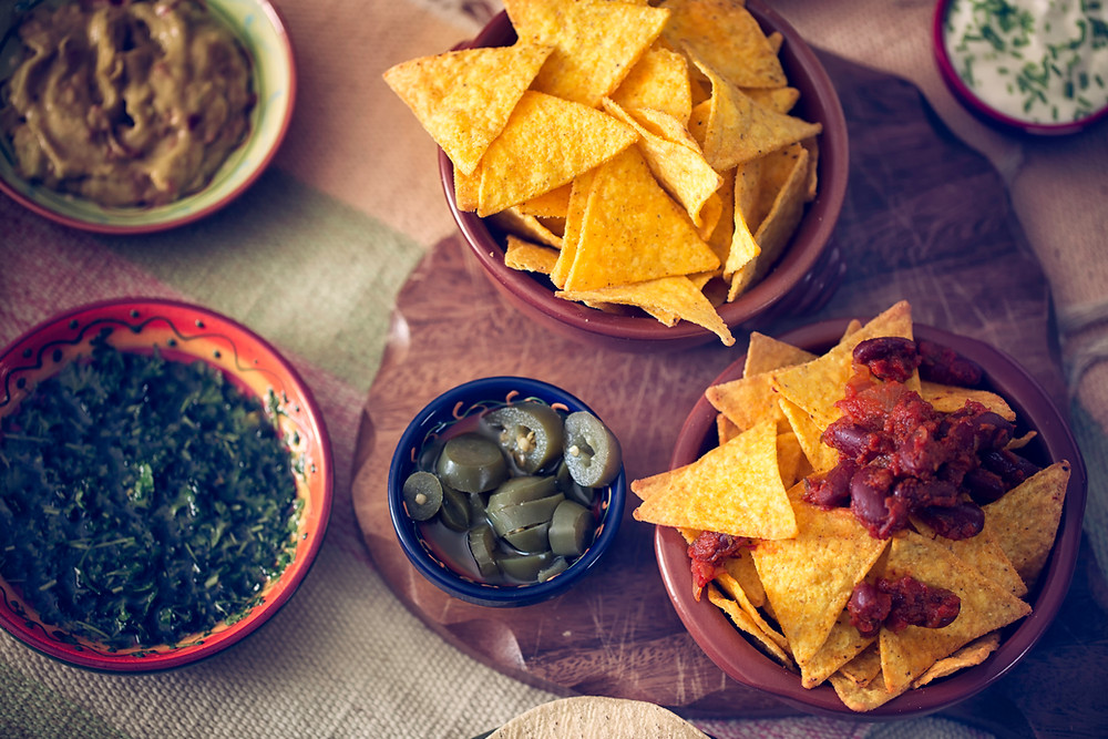 chips with two different salsas and a bowl of jalapenos