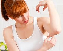 Hautstraffung mit Kosmetik am Oberarm einer Frau