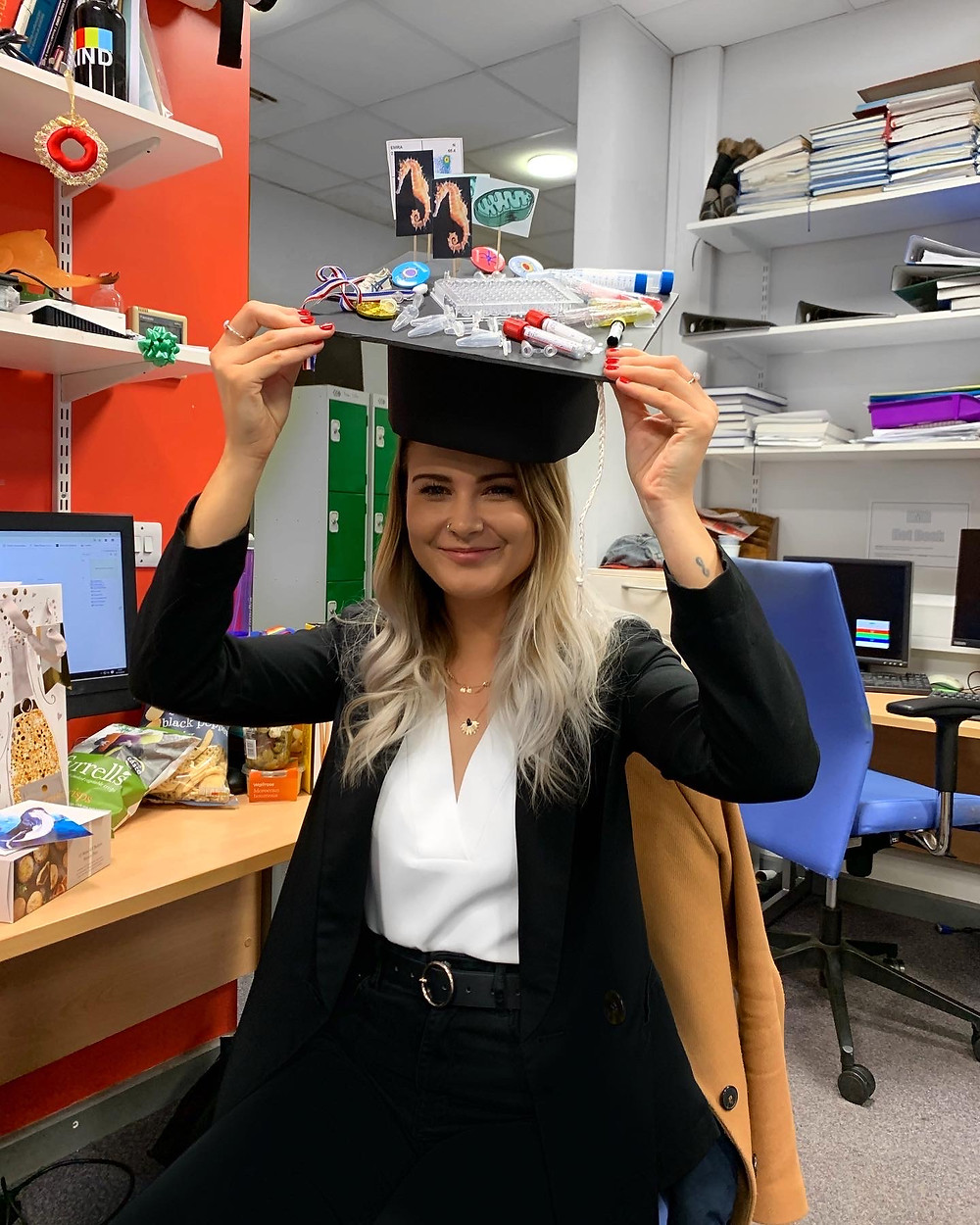 Lauren posing with a fake graduation hat after passing her PhD viva.