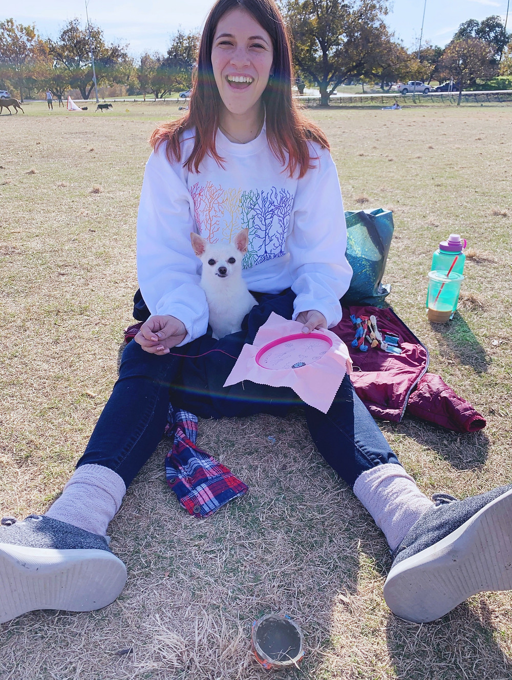Lauren sat in a park stitching with her dog.