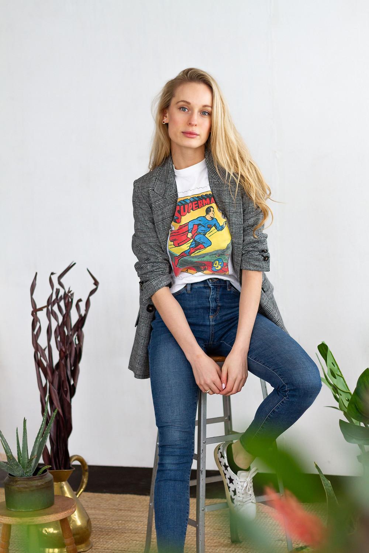 Tiff sat on stool wearing superwoman t-shirt.