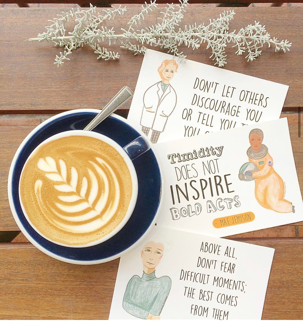 Postcards with diagrams of women in science and inspirational quotes.