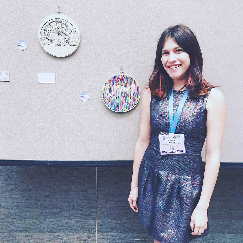 Photo of Lauren stood with some of her embroidery hoops.