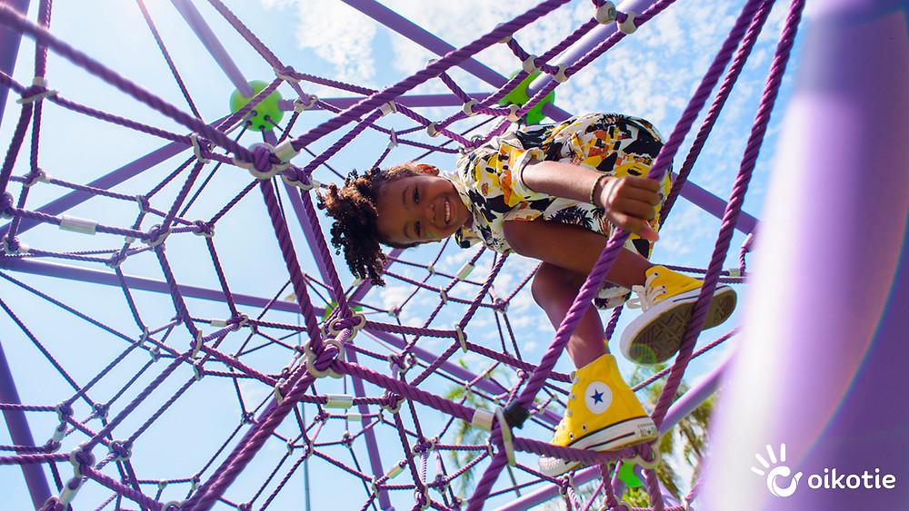 Menino com tênis amarelo, escalando equipamento de cordas da com roxa