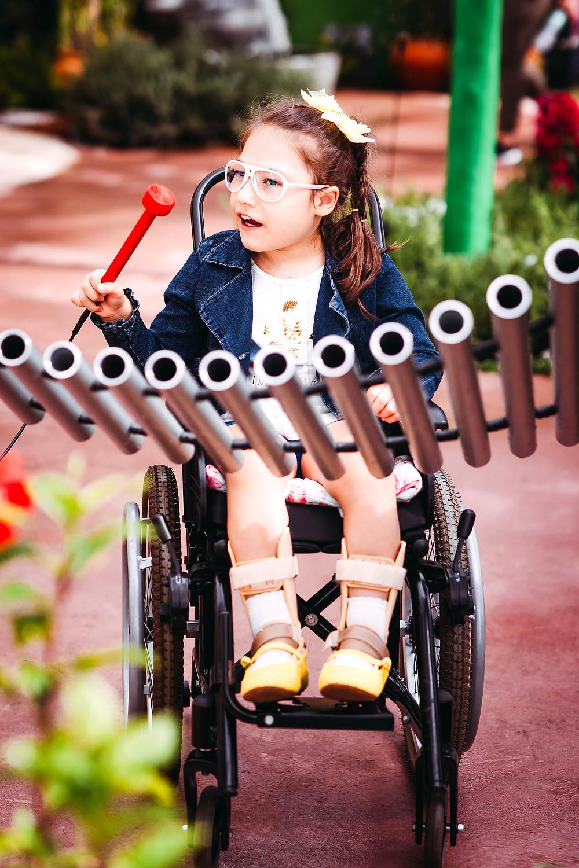Menina cadeirante brincando com instrumento musical