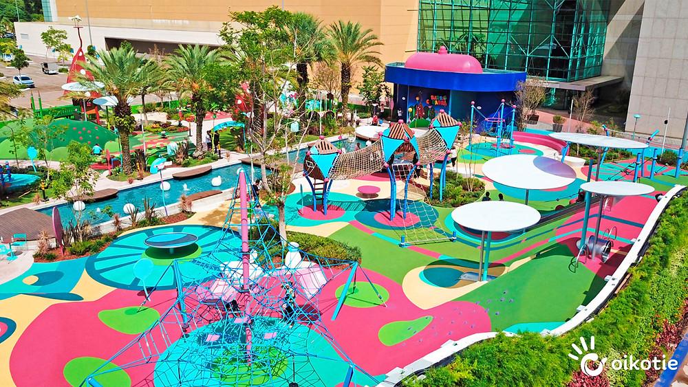 Parque de diversões ao ar livre, piso macio emborrachado, equipamentos de escalada, árvores. Cores predominantes, azul, rosa e amarelo.