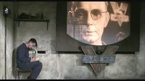Na imagem é possível ver o Winston em sua casa e uma grande teletela em funcionamento.