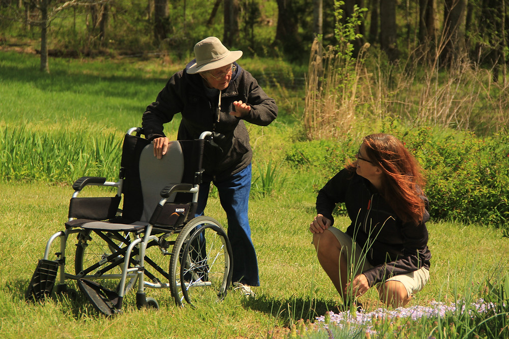 Miss Norma standing by her wheelchair in a garden telling Ramie a story