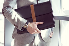 Businessman holding briefcase, close up