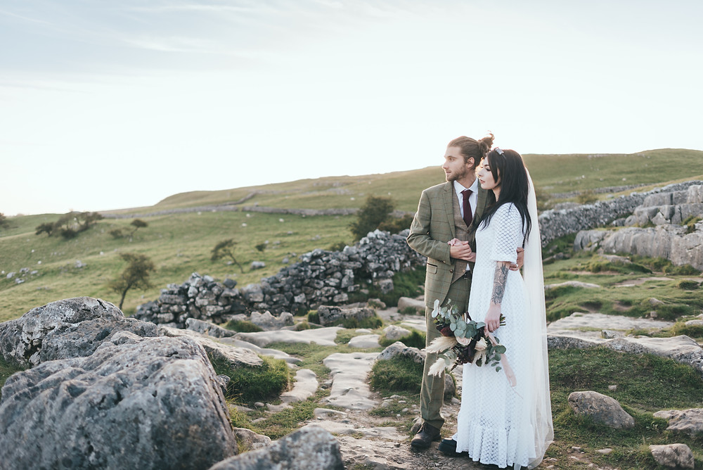 Bride and Groom look over the Yorkshire Dales as they get married at Malham Cove
