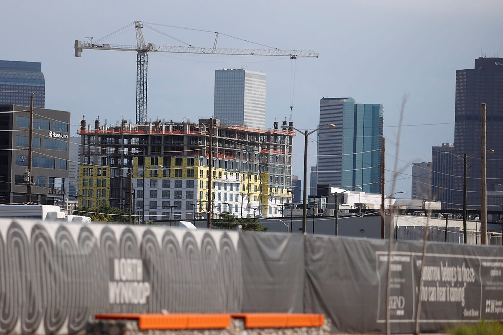 A crane hangs over a new housing development with the skyline in the background late Monday, June 22, 2020, in Denver.