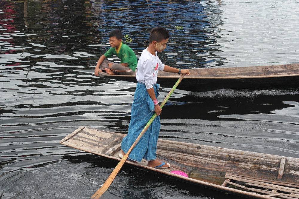 Cậu bé cuốn xà rông chèo thuyền bằng một chân trên hồ Inle