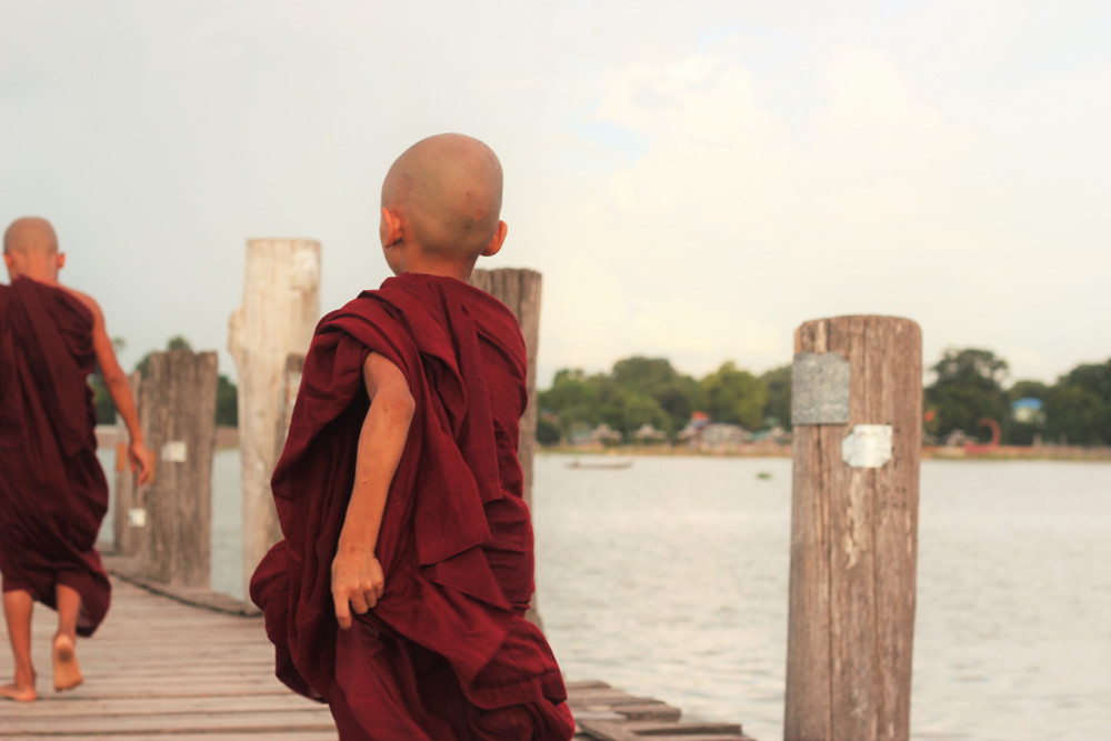 Một nhà sư nhỏ băng qua cầu gỗ Ubein - Mandalay Myanmar