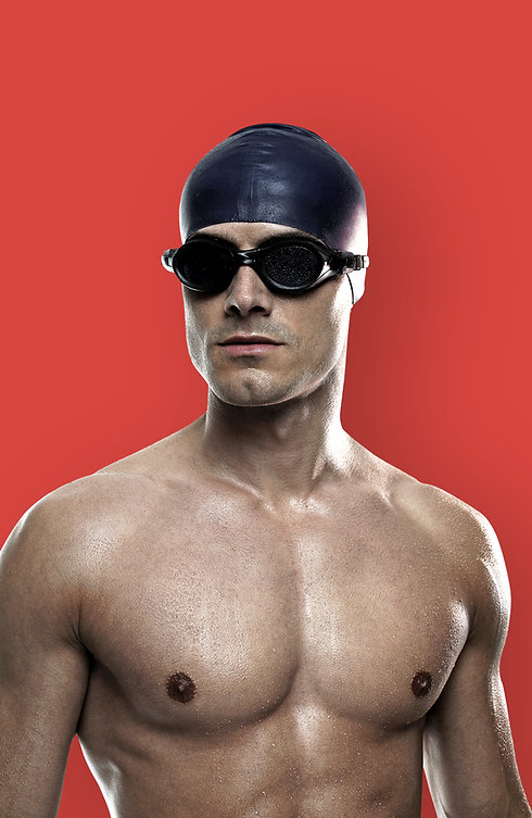 Male Swimmer with googles and a hat on looking forwards
