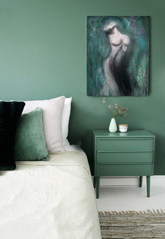 studies on teal bedroom wall over table.