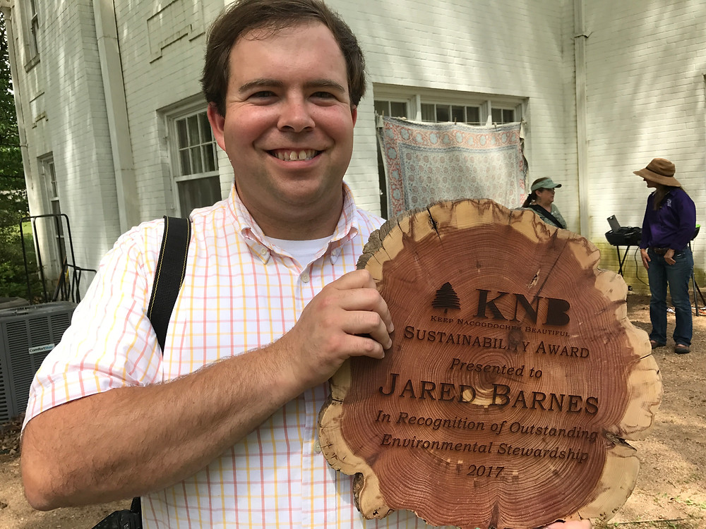 Dr. Jared Barnes hold the KNB Sustainibility Award.