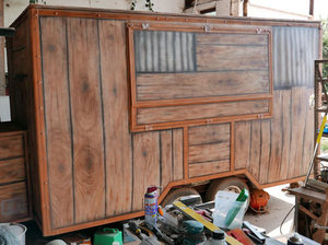 Food truck painted to look like wood and rusty corrugated metal