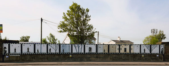 Full wall with trees and houses behind lined up with the work on the bridge