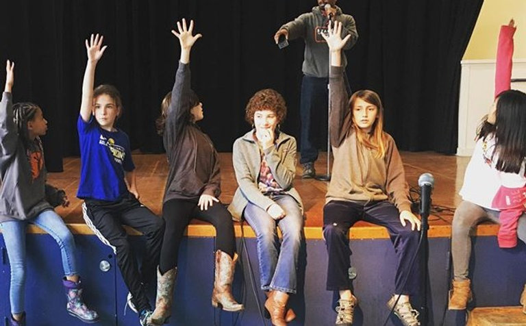 Middle school poets excitedly raise their hand during a poetry lesson