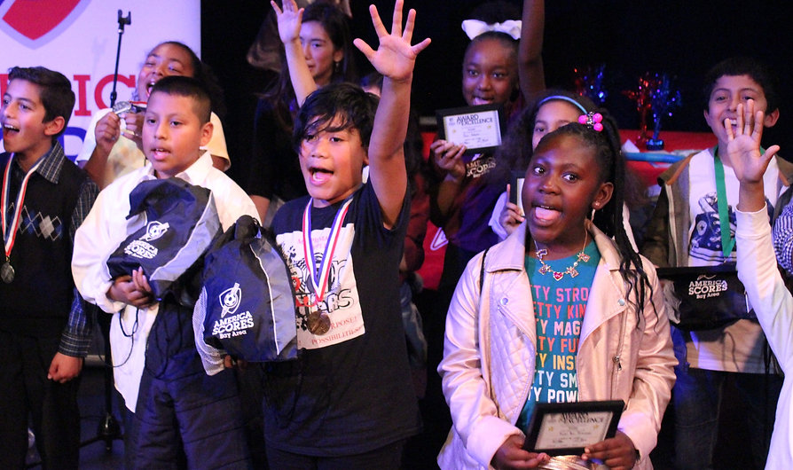Enthusiastic elementary school poets hold awards on stage after a poetry slam