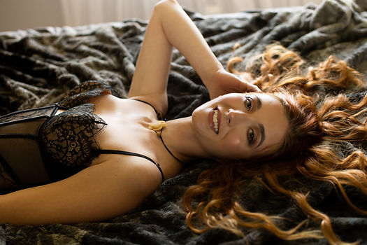 redhead, smiling, lying on back bed pose
