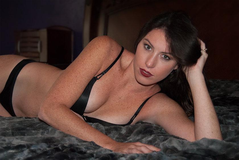 Brunette, red lipstick, freckles, black lingerie, side lying bed pose
