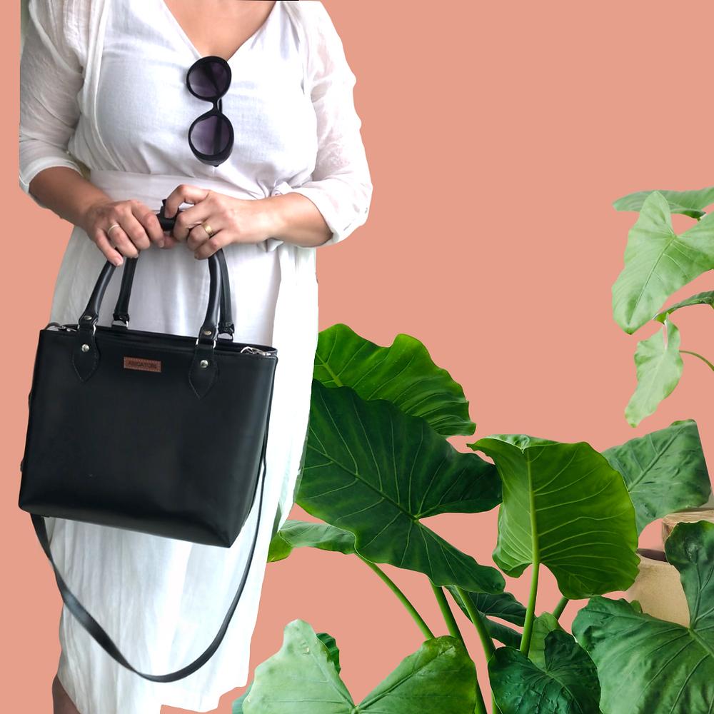 Mulher segurando bolsa preta em fundo rosa com plantas ornamentais decorativas