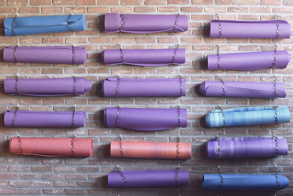 Brick wall with purple, blue and pink yoga mats on it