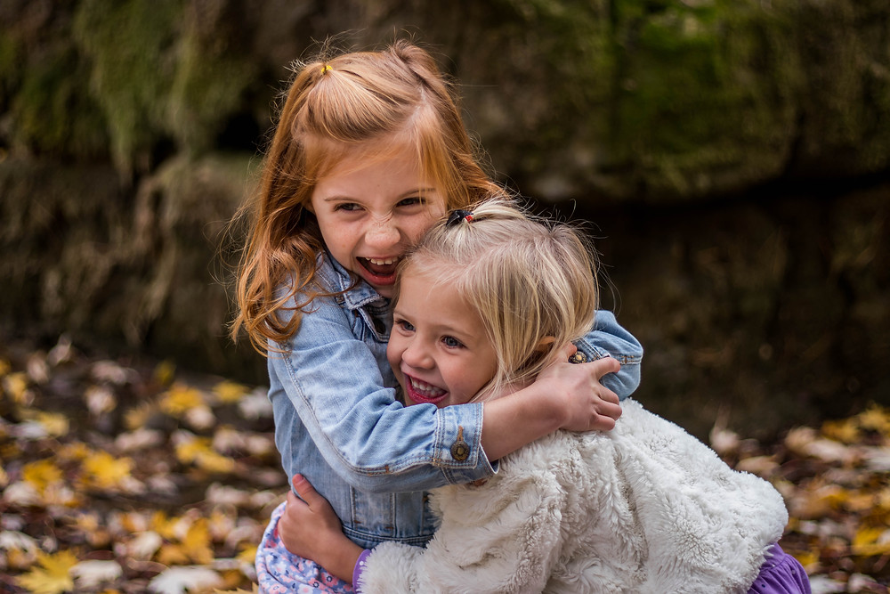 Two kids smiling and hugging