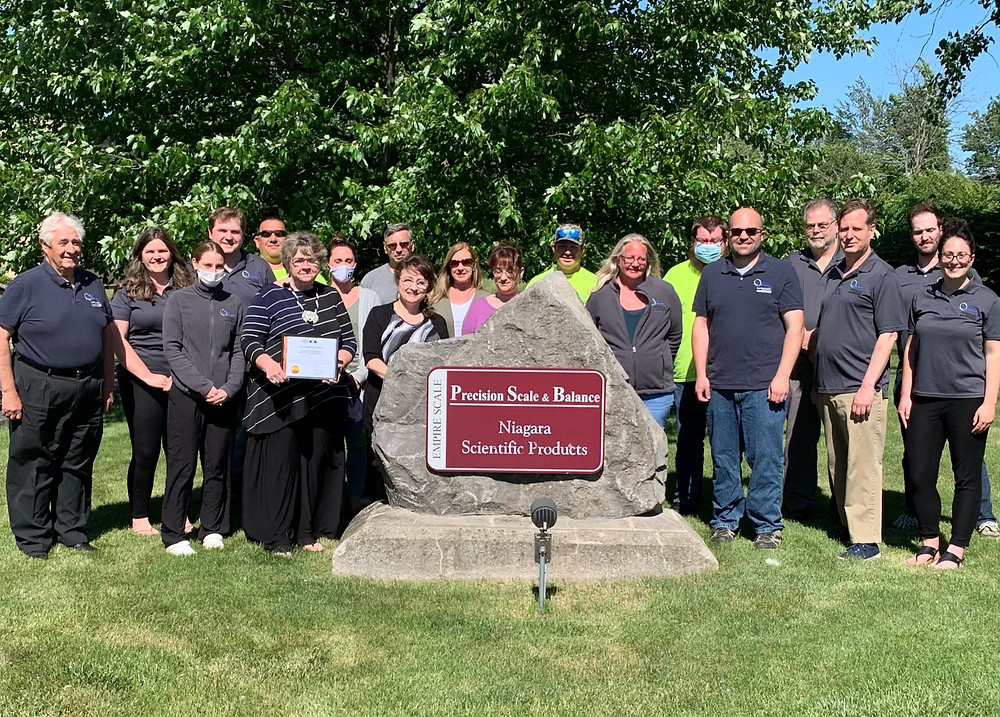 Employees at calibration company Precision Scale & Balance pictured front of company sign