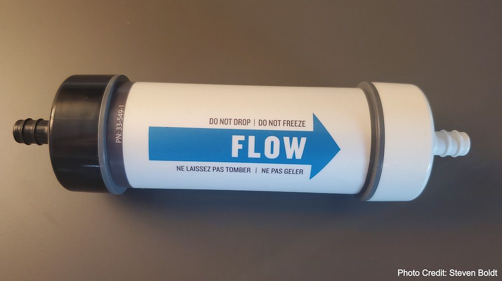 A water filter cartridge from Platypus GravityWorks 4L water treatment system showing the direction of flow by arrow.