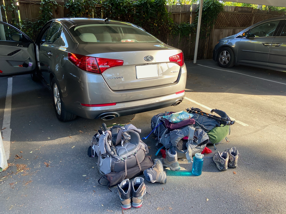 Backpacks, boots, trekking poles, and water bottles all laid out and ready for our hike in Trinity Alps Wilderness to Emerald and Sapphire Lakes.