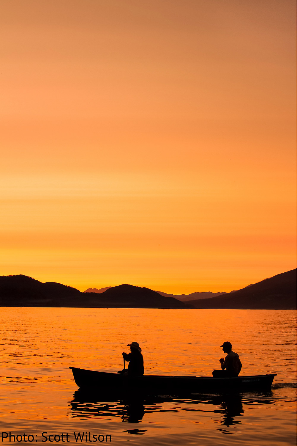 Two people in a canoe during sunset on Whitefish Lake in Northwestern Montana