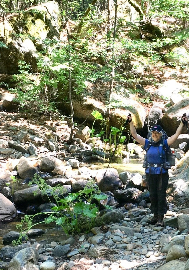 Hiker with trekking poles after crossing a creek on the Stuart Fork Trail in the Trinity Alps Wilderness.