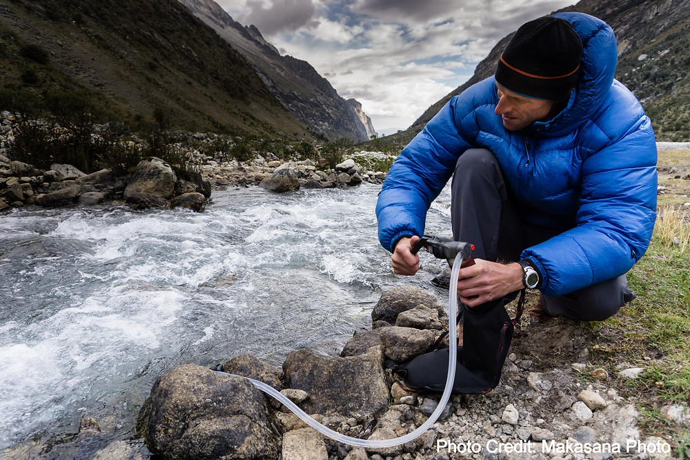 Person by a mountain creek, using an MSR Water Pump to treat water.