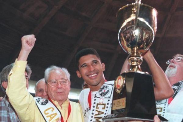 Crédito: Reprodução - Manoel Tobias com a taça da Liga Nacional ao lado do presidente Calçada