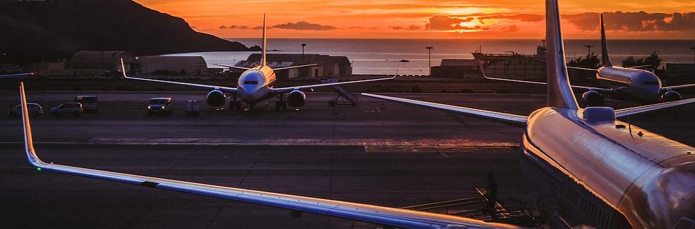 aviões parados ao entardecer em aeroporto à beira mar