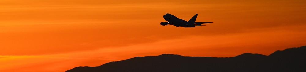 Avião Boeing 747 decolando no por do sol com céu laranja e montanha ao fundo.
