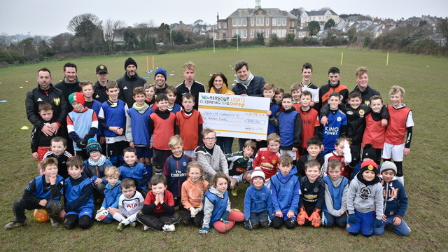 The team being presented with a cheque from Harbour Lights