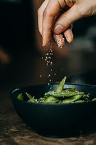 person-pouring-seasoning-on-green-beans-