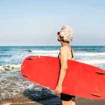 senior-woman-holding-a-surfboard-DHUWPX9