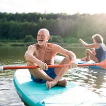 senior-couple-paddleboarding-on-lake-in-