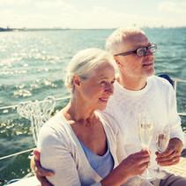 senior-couple-drinking-champagne-on-sail