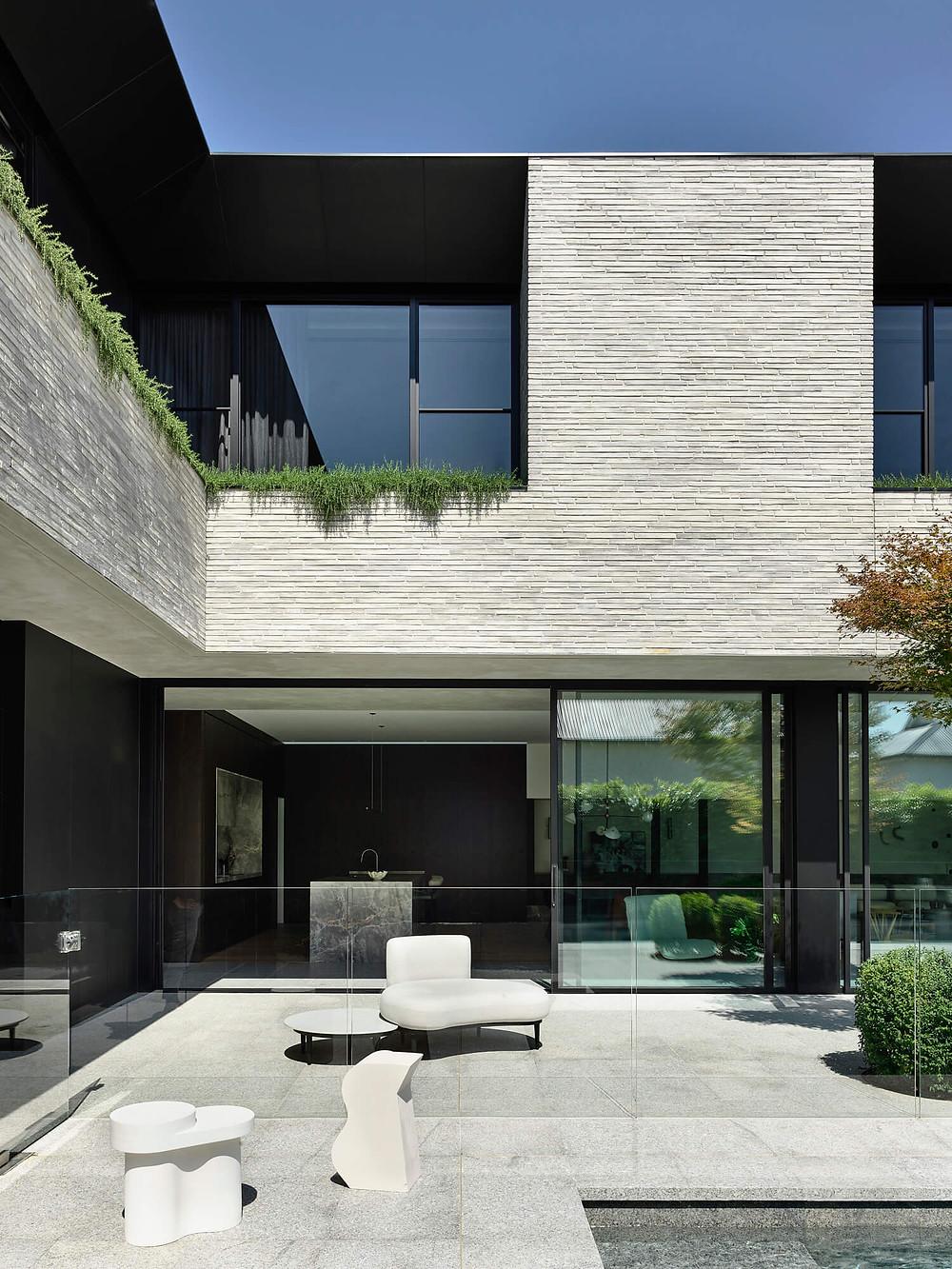 An elevated garden adds softness to the Petersen brick facade