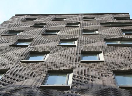 A rippled brick facade stops traffic in New York City