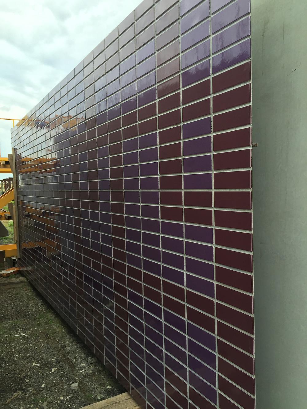 Magenta and cyan glazed brick tiles in a brick inlay facade