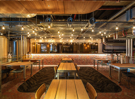 Brick tiles add warmth and tactile variation to the All Hands Brewing House