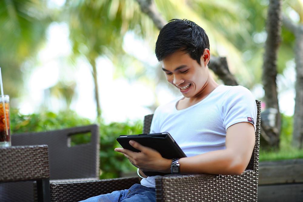 Man smiling at a tablet.