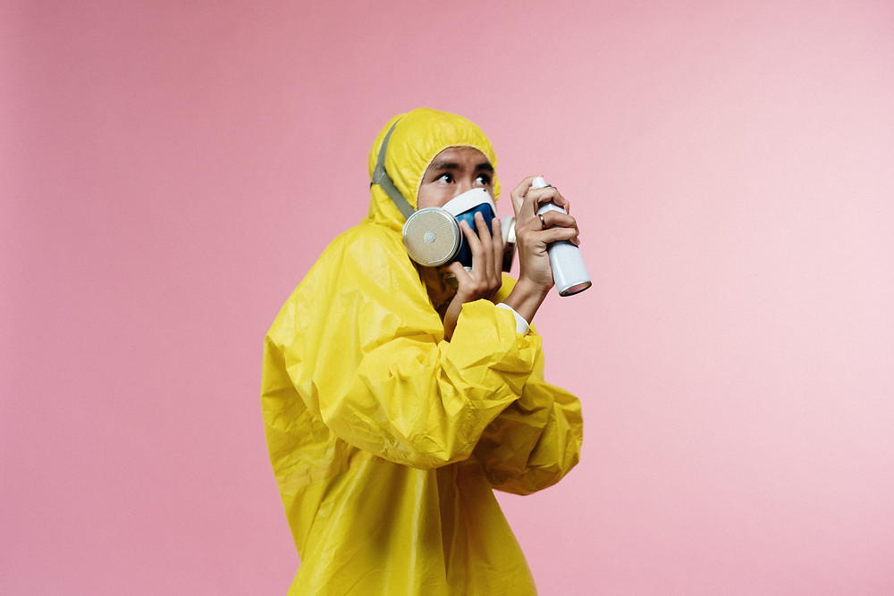 Man in HAZMAT suit holding a spray bottle.