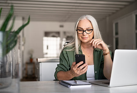 Happy senior woman using mobile phone wh